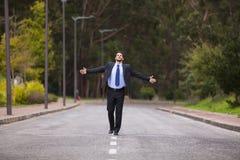 Hombre de negocios que camina en la línea del camino fotografía de archivo libre de regalías
