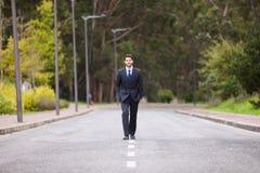 Hombre de negocios que camina en la línea del camino imagenes de archivo