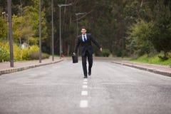 Hombre de negocios que camina en la línea del camino fotografía de archivo