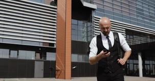 Hombre de negocios que camina en las calles del distrito financiero y que usa el teléfono móvil metrajes