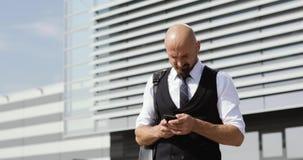Hombre de negocios que camina en las calles del distrito financiero y que usa el teléfono móvil almacen de metraje de vídeo