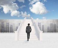 Hombre de negocios que camina en las escaleras Imagenes de archivo