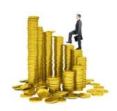 Hombre de negocios que camina en pilas de las monedas de oro Foto de archivo