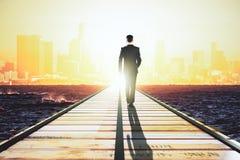 Hombre de negocios que camina en un camino recto a la ciudad grande en los sunris Imagen de archivo libre de regalías