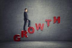 Hombre de negocios que camina encima de la escalera hecha de las letras que arreglan y x27; growth& x27; palabra Fotografía de archivo libre de regalías