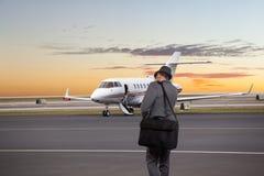 Hombre de negocios que camina hacia un jet privado Foto de archivo