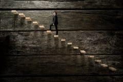 Hombre de negocios que camina para arriba en la escalera de madera Fotografía de archivo libre de regalías