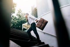 Hombre de negocios que camina para arriba en las escaleras y que sostiene la cartera fotografía de archivo