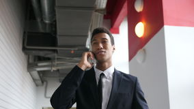 Hombre de negocios que camina Talking en el teléfono en la oficina, humor feliz almacen de video