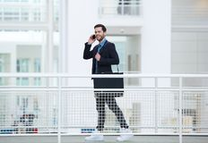 Hombre de negocios que camina y que habla en el teléfono móvil Foto de archivo libre de regalías