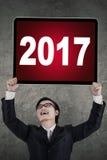 Hombre de negocios que celebra un Año Nuevo con el tablero Foto de archivo libre de regalías