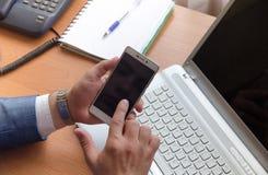 Hombre de negocios que celebra un smartphone y tactos su dedo índice Manos en el marco fotografía de archivo