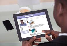 Hombre de negocios que charla en sitios sociales del establecimiento de una red Fotos de archivo