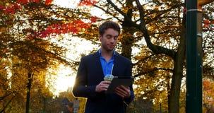 Hombre de negocios que come café mientras que usa la tableta digital metrajes