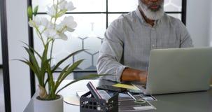 Hombre de negocios que come café mientras que usa el ordenador portátil en el escritorio 4k metrajes