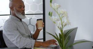 Hombre de negocios que come café mientras que usa el ordenador portátil en el escritorio 4k almacen de metraje de vídeo