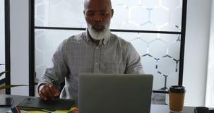 Hombre de negocios que come café mientras que usa la tableta gráfica en el escritorio 4k almacen de video