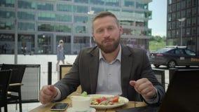 Hombre de negocios que come el almuerzo, sonriendo para la cámara, steadicam metrajes
