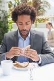 Hombre de negocios que come el bocadillo para el almuerzo Foto de archivo