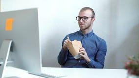Hombre de negocios que come la comida china mientras que teniendo una llamada de Internet almacen de metraje de vídeo