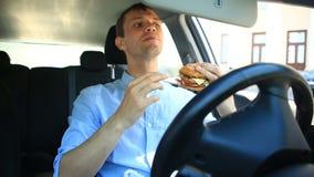Hombre de negocios que come los alimentos de preparación rápida mientras que se sienta en la rueda de un coche Hamburguesa almacen de metraje de vídeo