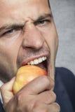 Hombre de negocios que come una manzana fotografía de archivo libre de regalías