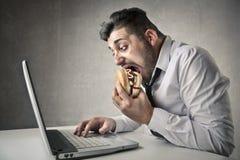 Hombre de negocios que come y que trabaja imagenes de archivo