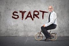 Hombre de negocios que comienza montando una bici Imagen de archivo libre de regalías