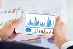 Hombre de negocios que compara gráficos en la tableta digital en el escritorio de oficina Foto de archivo