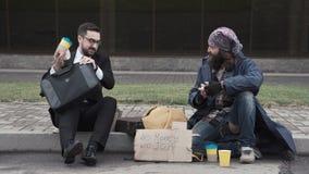 Hombre de negocios que comparte la comida a los desamparados almacen de video