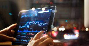 Hombre de negocios que comprueba datos del mercado de acción sobre la tableta