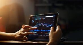 Hombre de negocios que comprueba datos del mercado de acción sobre la tableta Imagenes de archivo