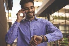 Hombre de negocios que comprueba el tiempo y la calle del canal que camina foto de archivo libre de regalías