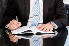 Hombre de negocios que comprueba encima de un diario Foto de archivo libre de regalías