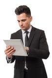 Hombre de negocios que comprueba la tableta para saber si hay noticias del mercado de acción Imagen de archivo libre de regalías