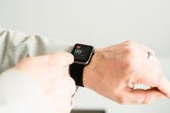Hombre de negocios que comprueba su pulso usando Apple imagen de archivo libre de regalías