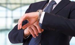 Hombre de negocios que comprueba tiempo en su reloj. Fotos de archivo libres de regalías