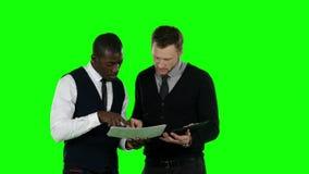 Hombre de negocios que considera la documentación Pantalla verde almacen de video