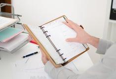Hombre de negocios que consulta su agenda imagenes de archivo