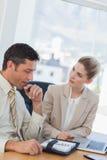 Hombre de negocios que consulta su orden del día mientras que habla con su colega Fotografía de archivo