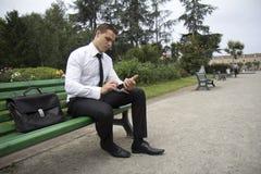 Hombre de negocios que consulta un teléfono móvil Foto de archivo libre de regalías