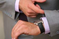Hombre de negocios que controla el reloj del tiempo Imágenes de archivo libres de regalías