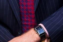 Hombre de negocios que controla el tiempo en su reloj Imágenes de archivo libres de regalías