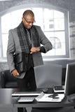 Hombre de negocios que controla tiempo en la oficina Imagen de archivo