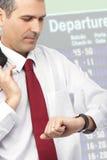 Hombre de negocios que controla tiempo en su reloj Imagen de archivo libre de regalías