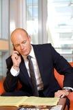 Hombre de negocios que conversa en el teléfono móvil mientras que lee el periódico Fotografía de archivo libre de regalías