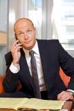 Hombre de negocios que conversa en el teléfono móvil, mirando para arriba Imágenes de archivo libres de regalías