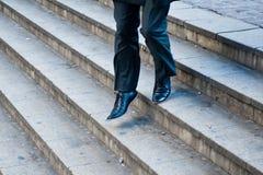 Hombre de negocios que corre abajo de las escaleras de la ciudad Foto de archivo libre de regalías