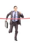 Hombre de negocios que corre con una cartera y que alcanza el final lin Fotos de archivo libres de regalías