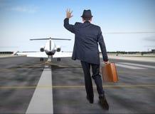 Hombre de negocios que corre detrás de un avión Imágenes de archivo libres de regalías